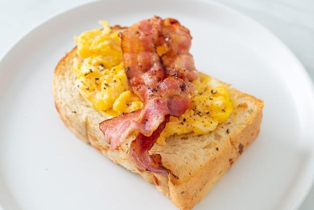 Pane tostato con uova strapazzate e pancetta su piatto bianco