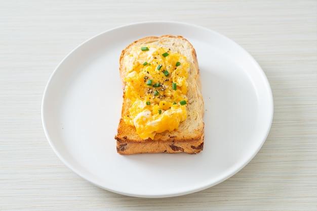 Pane tostato con uova strapazzate su piatto bianco