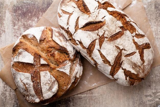 Pane, vista dall'alto, pagnotte nere e segale su fondo nero.