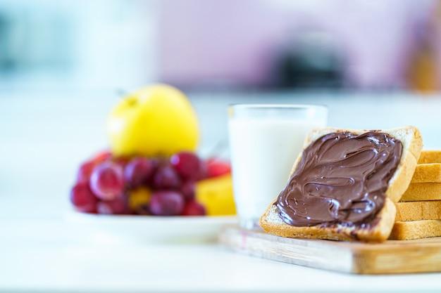Pane con pasta di cioccolato, frutta e un bicchiere di latte fresco per un dessert