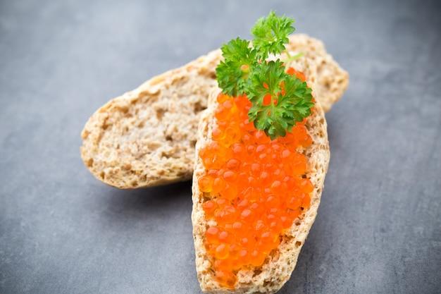 Pane con crema di formaggio fresca e caviale rosso sul tavolo.