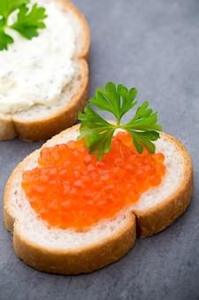 Pane con crema di formaggio fresca e caviale rosso sul tavolo