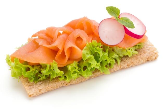 Pane con filetto di salmone fresco isolato su superficie bianca, vista dall'alto.