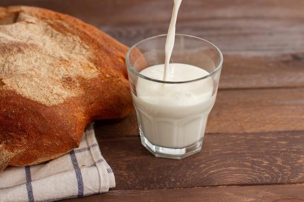 Pane con un bicchiere di latte sulla tavola di legno