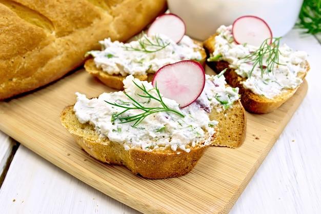 Pane con patè di ricotta, aneto e ravanello su una tavola di legno, un tovagliolo sullo sfondo del tavolo in legno