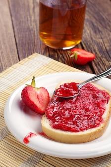 Pane con marmellata di fragole rosse e tazza di tè sul tavolo di legno