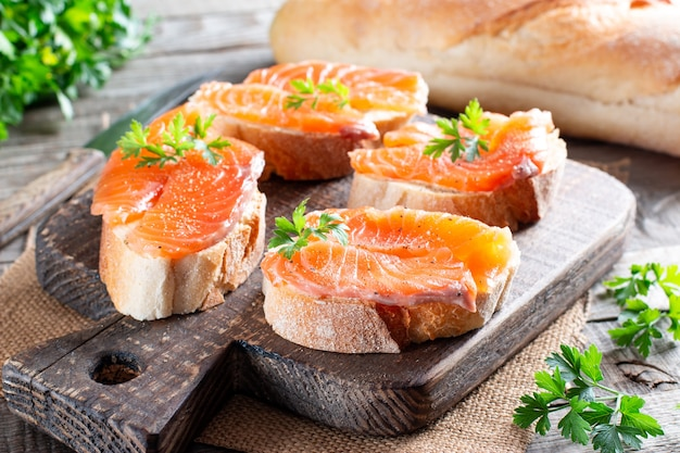 Pane con salmone affumicato e burro. deliziosi panini sul tavolo di legno