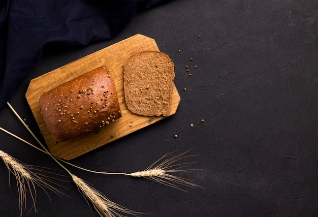Pane su una tavola di legno su uno spazio nero. copia spazio