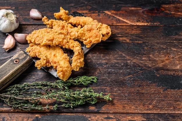Petto di pollo impanato a strisce. fondo di legno scuro. vista dall'alto. copia spazio.