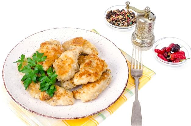 Pezzi di filetto di pollo impanati sulla piastra.