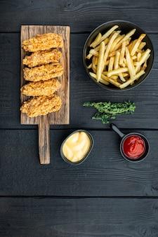 Tagli di ali di pollo impanate sulla tavola di legno nera, laici piana, con lo spazio della copia.