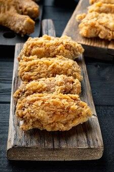 Tagli di ali di pollo impanate sulla tavola di legno nera