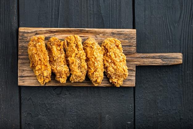 Tagli di ali di pollo impanate su legno nero