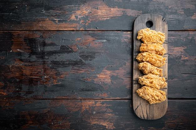 Tagli di ali di pollo impanate sul tavolo di legno scuro, vista dall'alto.