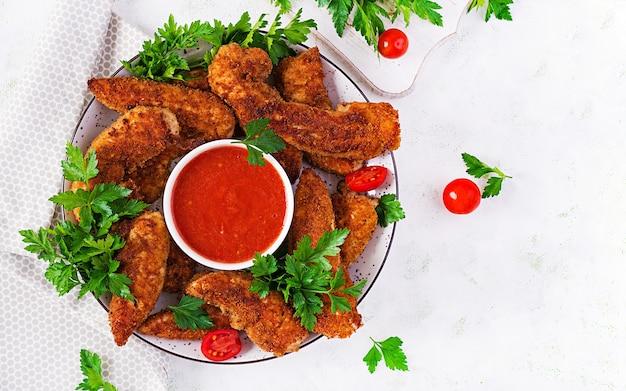Mini filetti di pollo impanati serviti con salsa di pomodoro. cibo americano. bocconcini di pollo con prezzemolo. vista dall'alto, copia dello spazio