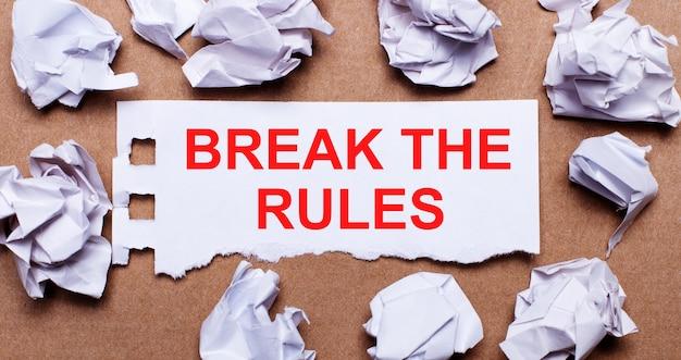 Break the rules scritto su carta bianca su sfondo marrone chiaro.