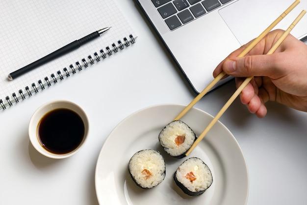 Pausa per mangiare sushi. rotoli di sushi snacking al lavoro.