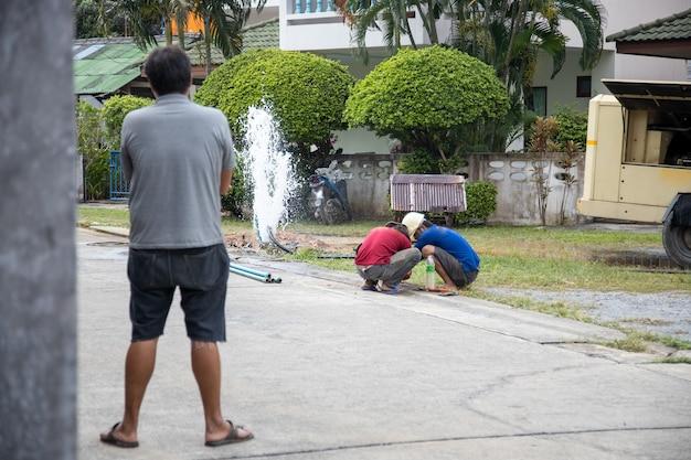 Rottura del tubo dell'acqua. l'acqua sta versando in una fontana. i lavoratori delle utility tengono la chiave inglese e in trincea riparano il seme rotto.