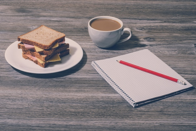 Pausa al lavoro. panino al formaggio con tazza di caffè bianco, taccuino e matita. vista orizzontale, fondo in legno grigio