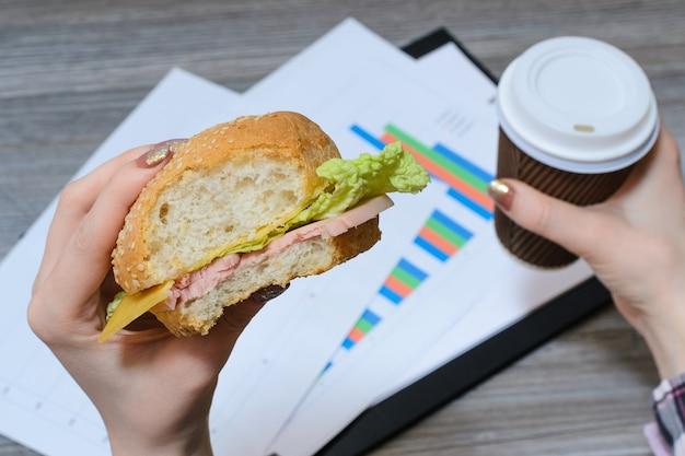 Pausa al lavoro. operaio affamato che mangia cheeseburger e beve caffè