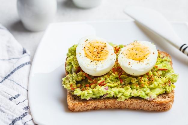 La colazione avocado toast con uovo su una piastra bianca, sfondo bianco.