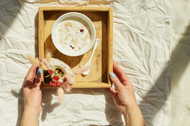 Colazione a letto, mani femminili provate con ciotola di muesli, muesli e fiori alla luce del sole a casa, cameriera che porta vassoio con colazione in camera d'albergo, buon servizio
