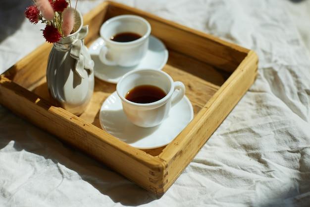 Colazione a letto, prova con due tazze di caffè e fiori alla luce del sole a casa, cameriera che porta vassoio con colazione in camera d'albergo, buon servizio