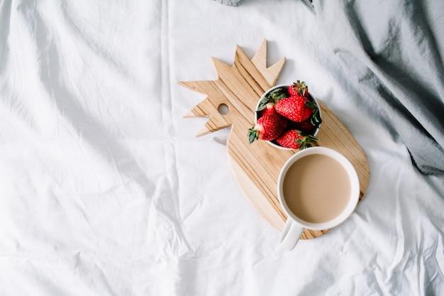 Colazione a letto con tazza da caffè e fragola. lenzuola grigio chiaro. disposizione piana, vista dall'alto.