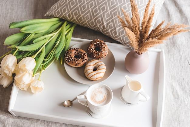Faccia colazione a letto con la tazza con cappuccino, ciambelle e tulipani bianchi