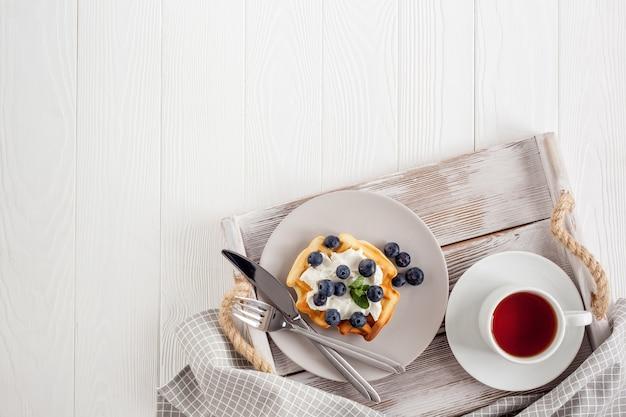 La colazione a base di cialde belghe sul tavolo servito su legno bianco