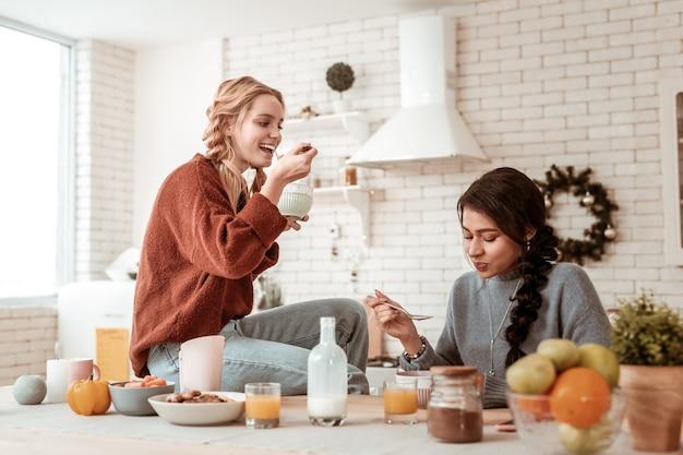 Ciotola per la colazione. attrarre ragazze positive che trasportano grandi cucchiai e mangiano cereali indossando maglioni caldi