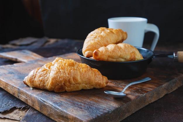 Pane per la colazione, croissant e latte fresco sul tavolo di legno.