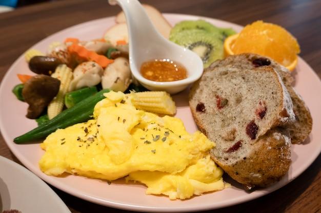 Colazione a base di pane, verdura e frutta su un piatto al mattino