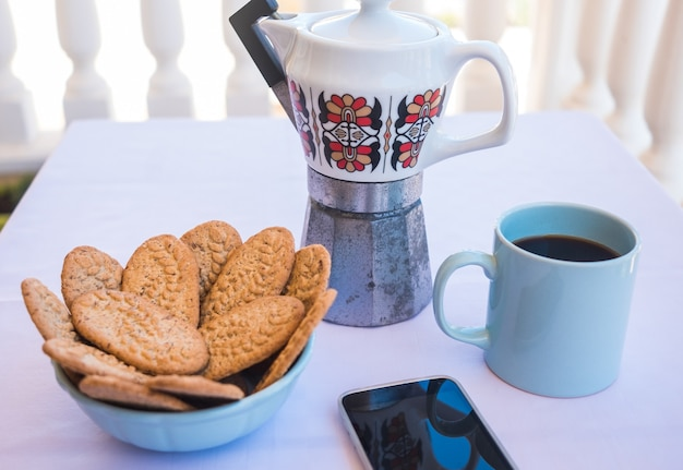 Colazione o pausa all'aperto sul balcone con tazzina da caffè e biscotti integrali. caffettiera vintage in ceramica. cellulare all'angolo