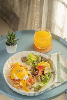 A colazione o brunch, le uova alla benedict servono con pancetta fritta e pane tostato e insalata di verdure per contorno in un piatto bianco o piatto su un panno bianco con striscia verde e vengono con succo d'arancia