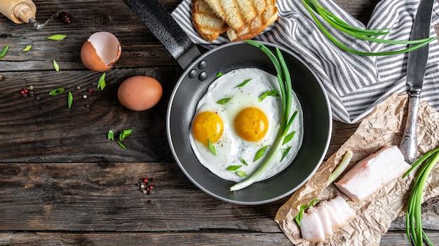 Colazione o brunch con pancetta fritta e uova in padelle nere e toast croccanti vista dall'alto