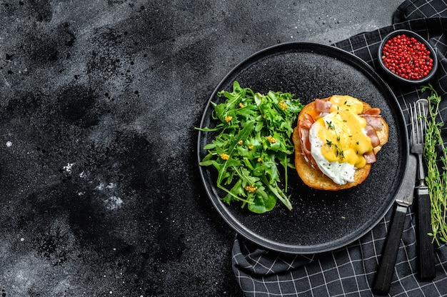 Hamburger da colazione con pancetta, uovo alla benedict, salsa olandese su pan brioche.