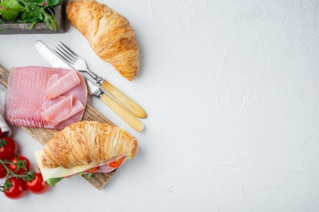 Colazione, pranzo di lavoro, panini set di croissant, con erbe e ingredienti, su pietra bianca sullo sfondo, vista dall'alto laici piatta, con copia spazio per il testo