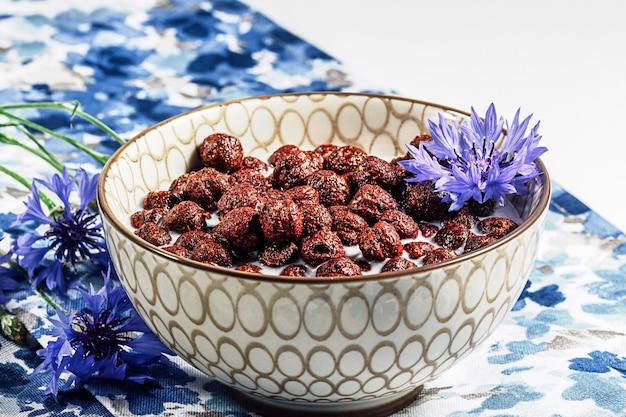 Cereali per la colazione, cereali al cioccolato nel latte con fiori di fiordaliso su un tovagliolo blu naturale, concetto di alimentazione sana per i bambini.