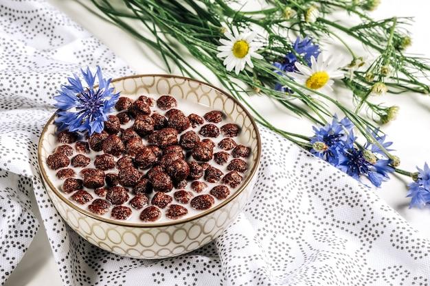Cereali per la colazione, cereali al cioccolato nel latte con fiore di fiordaliso su un tovagliolo bianco, concetto di alimentazione sana per i bambini prima della scuola.