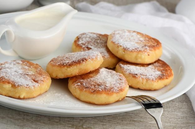 Colazione. frittelle di formaggio con panna acida cosparse di zucchero a velo su un piatto bianco.