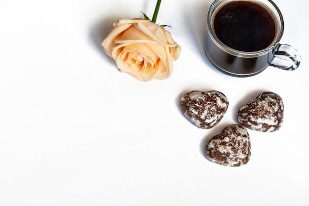 Colazione, caffè, torte al cioccolato a forma di cuori e una rosa gialla su sfondo bianco, copia dello spazio