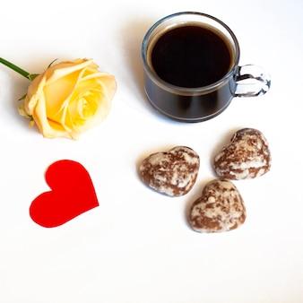 Caffè della colazione, torte al cioccolato a forma di cuori e una rosa gialla su sfondo bianco e cuore rosso
