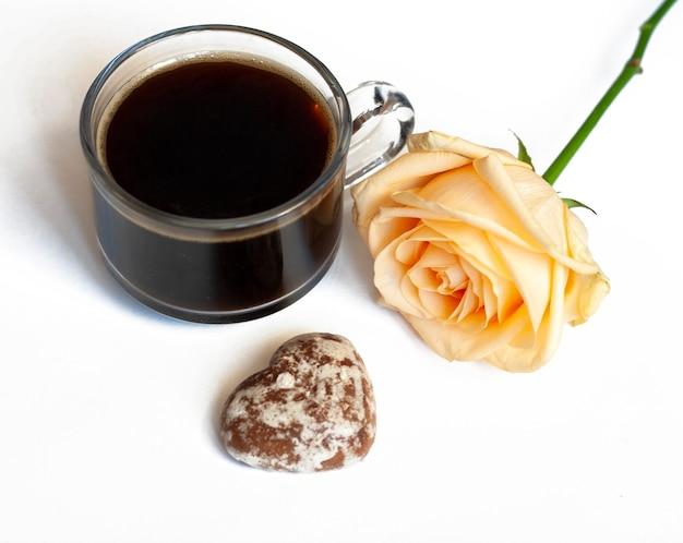 Colazione, caffè, torte al cioccolato a forma di cuori e una rosa gialla su sfondo bianco