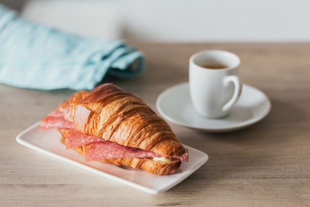 Colazione a base di caffè e panino con cornetto farcito con salame