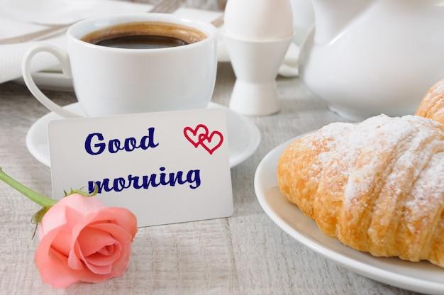 Colazione a base di croissant farciti al cioccolato tazza di caffè mattutino e un biglietto con un augurio buongiorno