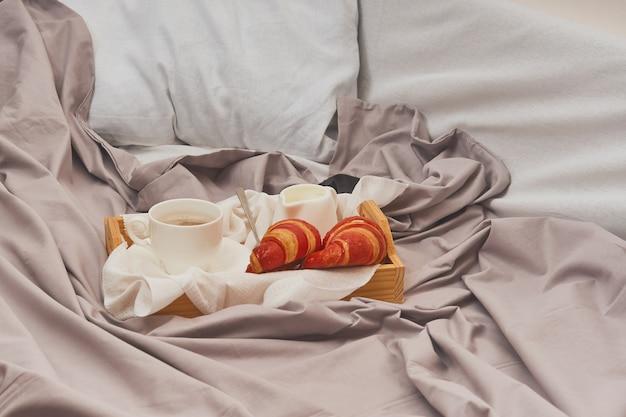Colazione su un letto sgualcito, caffè, croissant, libro,