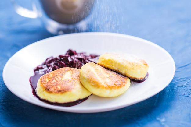 Colazione e delizioso concetto - frittelle di ricotta con marmellata, sfondo blu. cospargere