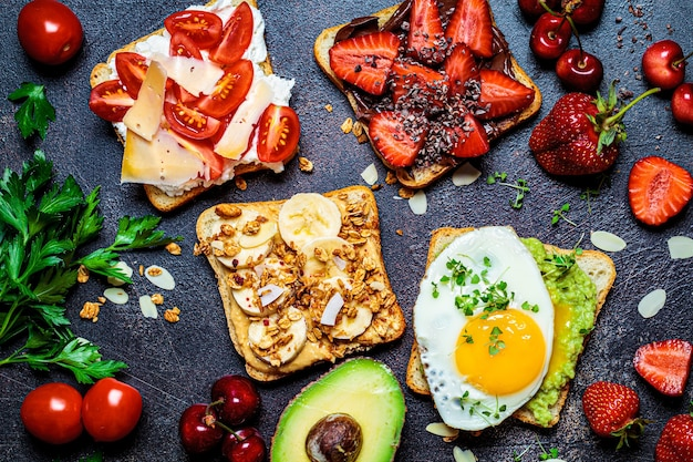 Colazione diversi toast con frutti di bosco, formaggio, uova e frutta, sfondo scuro, vista dall'alto. concetto di tavolo per la colazione.