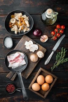 Gli ingredienti delle uova per la colazione si mescolano, sul vecchio tavolo di legno scuro dark